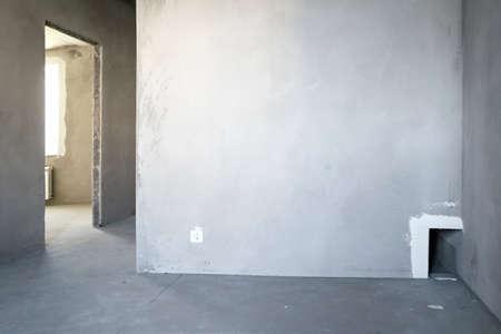 Photo pour Unfinished building. Rough finish of the apartment. A large empty room with plastered concrete walls. Interior renovation. - image libre de droit