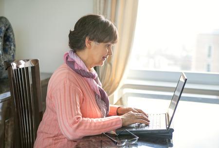 Foto für Elderly good looking woman working on laptop. Portrait in domestic interior - Lizenzfreies Bild