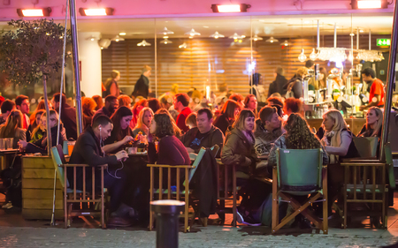 Photo for London, UK - December 19, 2015:  People in the restaurant, well lit up outside patio - Royalty Free Image