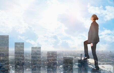 Photo pour Young woman climbing up on the growth bars and looking positive to the future. Blue sky and sunshine. Business, success and strategy concept - image libre de droit