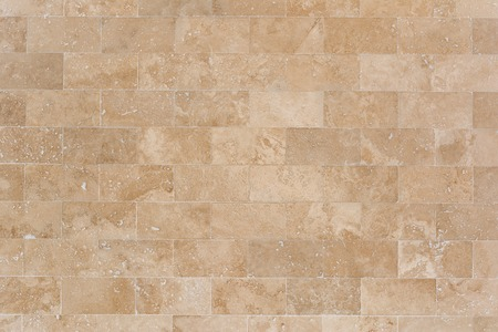 Stone facing of beige wall made of travertine. Texture of masonry.