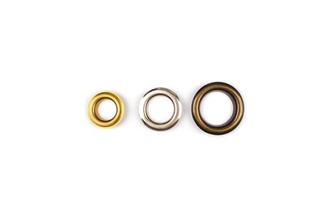 Photo pour Three brass multicoloured metal eyelets or rivets - curtains rings for fastening fabric to the cornice, isolated on white. With copyspace for text for your presentation - image libre de droit