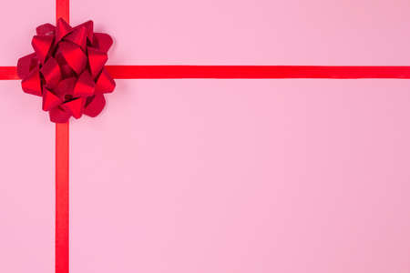 Photo for Flat lay composition with decorative red ribbon bow on pink background with copy space for text. Giving presents concept. Greeting card or holidays sale background, selective focus - Royalty Free Image