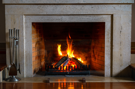 Photo pour Wood burning in a cozy fireplace at home in interior. Fireplace as a piece of furniture. Christmas New Year concept decorations. - image libre de droit