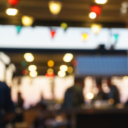 Photo pour Blurred  of customer men sitting at restaurant, bar or night club, with bokeh and bright light bulbs. - image libre de droit