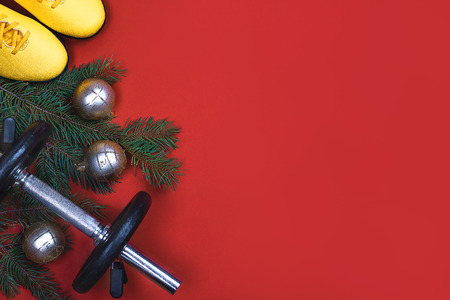 Photo for Exercise, Fitness, sport and Working Out Merry Christmas and Happy new year background with dumbbells, yellows sneakers, branches fir tree, holiday decorations on red background. Copy space. Flat lay. - Royalty Free Image