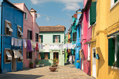 Colorful houses by canal in Burano, Venice, Italy. Burano is an island in the Venetian Lagoon and is known for its lace work and brightly colored homes.