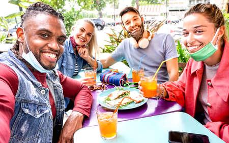 Photo pour Friends taking selfie in a bar restaurant with face mask - image libre de droit