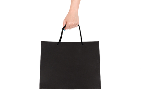 Black shopping bag in female hand isolated on white background.