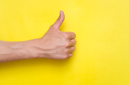 Foto de Male hand showing a thumbs up gesture isolated on yellow background. - Imagen libre de derechos