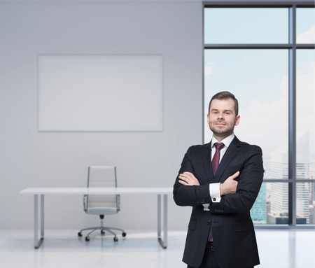 Smiling handsome businessman in a black suit with the crossed arms. Modern workplace in an office. New York view.