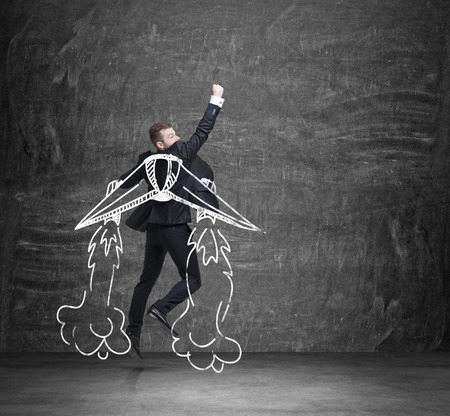 A concept of business angel. A businessman is flying over the black chalkboard.