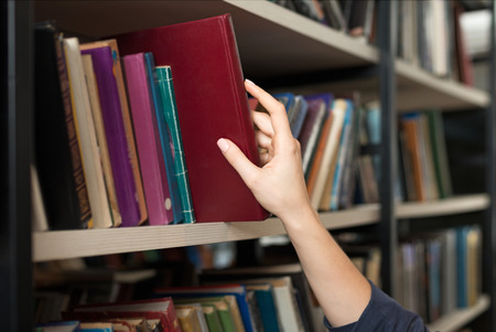 a book picked or taken with a hand from a book shelf in the library, a concept of learning and choice