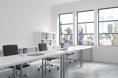 A row of tables leading to windows in an open space office. Computers on them, shelves with folders behind. New York view in windows. Concept of a modern office. 3D rendering