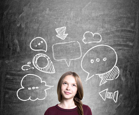 Young woman with thought and speech bubble sketches thinking about something on chalkboard background