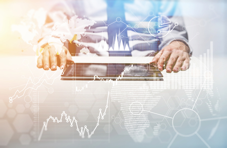 Businessman using pad with abstract financial charts and map at office desktop. Global business concept