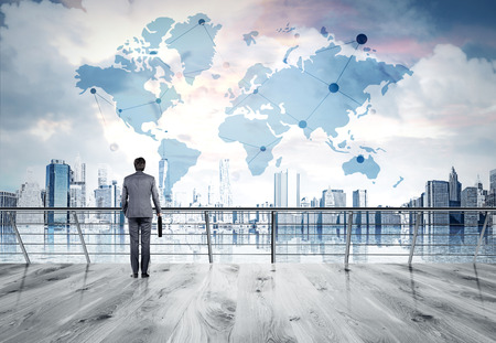 Businessman in suit standing on bridge, looking at New York city thinking about perspectives. Consept of business success. Sketch of world map at background. Elements of this image furnished by NASA.