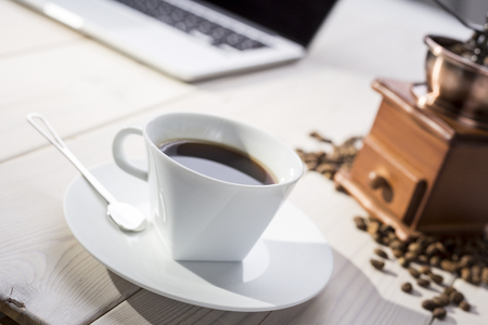 Close up of a cup of coffee with a saucer and a spoon. Coffee grinder and beans are lying near a laptop on wooden desk