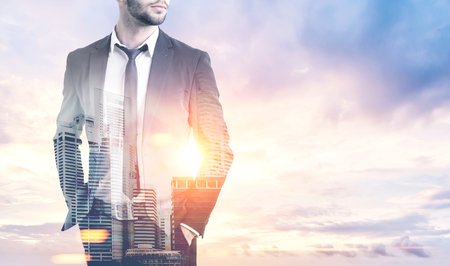 Portrait of an unrecognizable young businessman standing with his hands in pockets against a morning sky background. City view is in the foreground. Toned image double exposure mock up