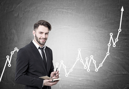 Portrait of a smiling young bearded businessman in a black suit and a tie holding a planner and a pen and looking at the viewer. He is standing near a blackboard with a rising graph
