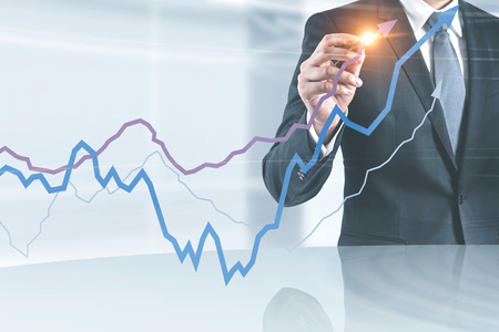 Unrecognizable businessman in dark suit drawing graphs with glowing pen standing in his office. Stock market concept. Toned image double exposure
