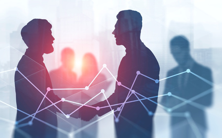 Silhouettes of business people shaking hands with their colleagues in background standing in blurred city with double exposure of graphs. Toned image