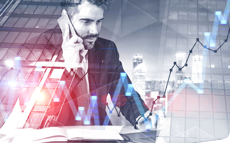 Portrait of calm young businessman talking on smartphone and typing at laptop sitting at office table. Night cityscape background with graphs. Toned image double exposure