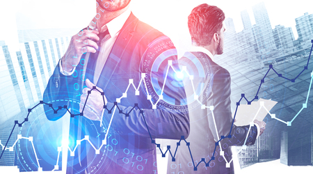 Two young brokers standing together over cityscape background with graphs and HUD interface. Stock market analysis concept. Toned image double exposure