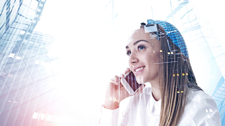 Foto de Smiling young woman in white shirt talking on smartphone. Double exposure of abstract cityscape. Concept of business communication. Toned image - Imagen libre de derechos