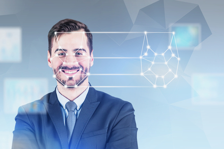 Foto de Cheerful young man in suit using facial recognition and biometric verification technology. Concept of security check and machine learning. Blurred gray background. Double exposure - Imagen libre de derechos