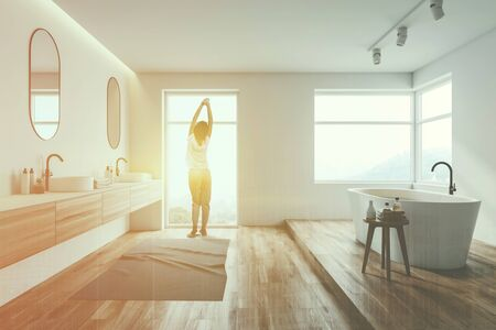 Photo pour Rear view of woman in pajamas standing in luxury white bathroom interior with wooden floor, large windows, comfortable bathtub and double sink. Toned image double exposure - image libre de droit