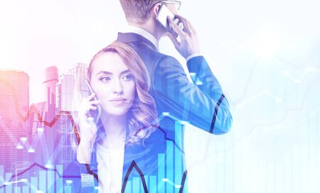 Serious young businesswoman with red hair and her colleague in glasses talking on smartphone over city background with double exposure of graph. Concept of stock market. Toned image
