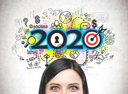 Photo pour Close up of astonished young woman head near concrete wall with colorful 2020 business strategy sketch. Concept of planning and new year resolutions - image libre de droit