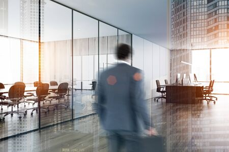 Photo for Blurry businessman entering modern open space office with white and wooden walls and comfortable meeting room with wooden conference table. Toned image double exposure - Royalty Free Image
