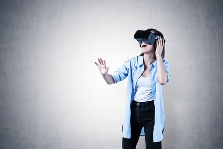 Photo for Portrait of happy young woman in casual clothes gesturing and having pleasant virtual reality experience over concrete wall background. Concept of hi tech and entertainment. Mock up - Royalty Free Image