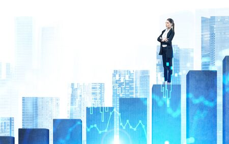 Foto de Confident young European businesswoman standing with crossed arms on big bar chart in abstract city with double exposure of blurry digital graph. Concept of investment and career ladder. Toned image - Imagen libre de derechos