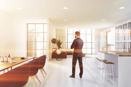 Photo for Young man in suit standing in panoramic open space kitchen with white walls, bar with stools, dining table with armchairs and living room with grey sofa in background. Blurry city. Toned image - Royalty Free Image