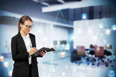 Photo for Smiling young businesswoman with glasses writing in her notebook in blurry office with double exposure of financial graphs. Concept of trading and market analysis. Toned image - Royalty Free Image
