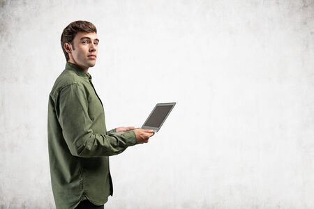 Foto de Side portrait of inspired young college student or computer guy in green shirt holding laptop near concrete wall. Concept of internet, communication and education. Mock up - Imagen libre de derechos