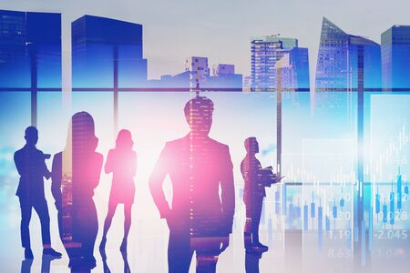 Foto de Silhouettes of business people in blurry panoramic office with double exposure of abstract cityscape and financial graph. Concept of stock market and investment. Toned image - Imagen libre de derechos