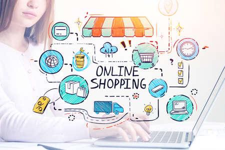 Foto de Unrecognizable young businesswoman using laptop with double exousre of colorful online shopping sketch. Toned image - Imagen libre de derechos