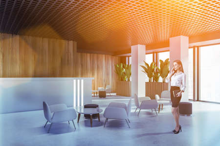 Foto de Businesswoman talking on smartphone in office waiting room with wooden walls and armchairs. Toned image - Imagen libre de derechos
