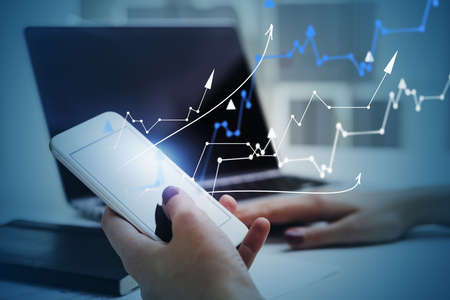 Foto de Hands of businesswoman using smartphone and laptop in blurry office with double exposure of financial graphs. Toned image - Imagen libre de derechos