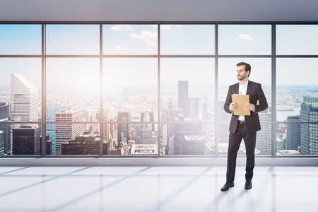 Photo for Portrait of young businessman with clipboard standing in empty panoramic office. Concept of paperwork and leadership. Toned image - Royalty Free Image
