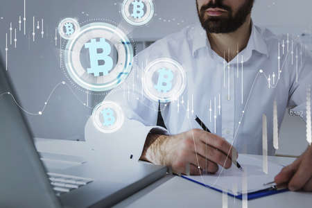 Foto de Businessman wearing formal suit is looking at laptop and putting down notes, analyzing and predict the behavior of cryptocurrency market. Forex candlestick, bitcoin logotype, office background - Imagen libre de derechos