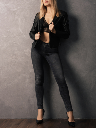 Fashion girl. Beautiful glamour stylish model in leather jacket, , jeans, high heels. Young Caucasian woman posing in studio.