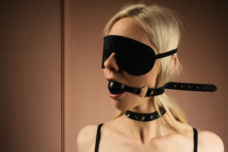 Photo pour sexy lady in bdsm outfit. Close-up girl in mask and collar with gag in mouth -Image - image libre de droit