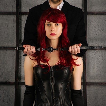 Foto de Adult sex games. A man holds a gag near the mouth of a red-haired girl in a leather corset. Bdsm outfit - Imagen libre de derechos