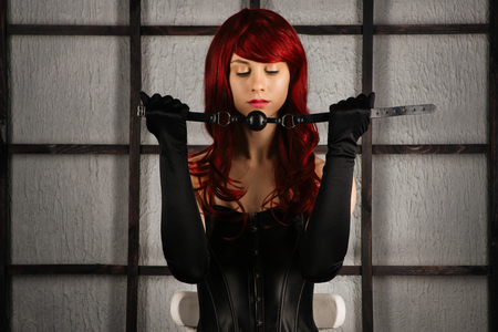 Foto de Red-haired girl in a leather corset holds a gag near the mouth. Bdsm outfit - Imagen libre de derechos