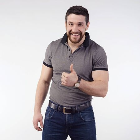Photo for Happy smiling winking young man with thumbs up. Full body length portrait isolated over gray background. - Royalty Free Image